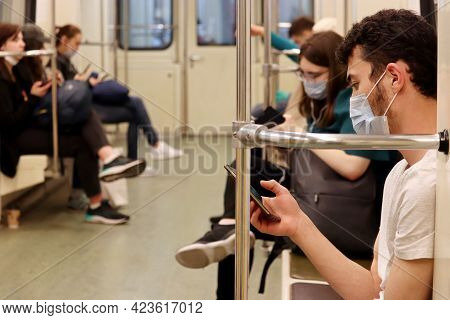 Moscow, Russia - June 2021: Crowd Of People In A Metro Train, Passengers In Masks Sits With Smartpho