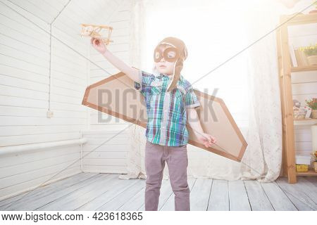 Children Boy Wearing Pilot Costume Making Ready To Fly Gesture Standing On Living Room Wooden Floor