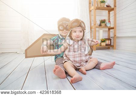 Happy Children Playing With Vintage Wooden Airplane. Kids Having Fun At Home. Imagination And Freedo