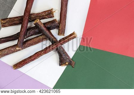 Dog Treat Sticks Randomly On A Colorful  Background. A Group Of Chewy Goodies. Dried Beef Esophagus.