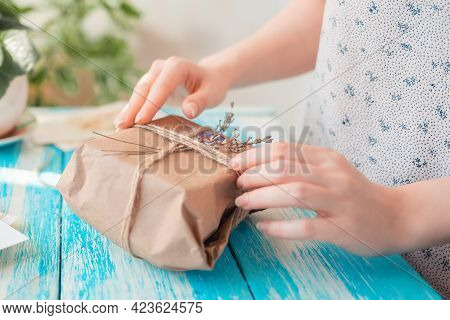 A Woman Packs A Parcel In Craft Paper Wrapped With Twine With Dried Flowers. Hands Close-up. Concept