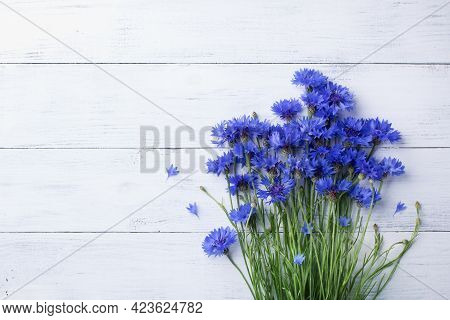 Bunch Of Blue Cornflowers On White Wooden Table Top View.