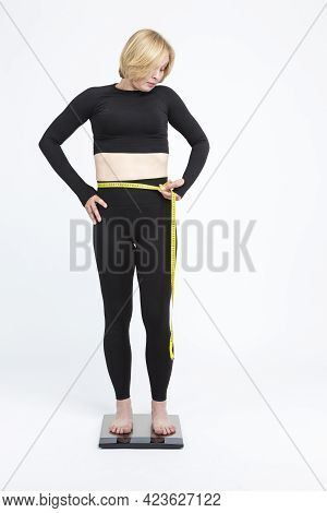 Weight Ideas. Mature Caucasian Woman Checking Her Weight With Floorstanding Weigh-scales. Vertical I