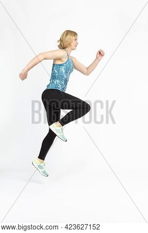 Senior Woman Sport Ideas. Running Fitness Mature Sportswoman During Active Jogging Training Against