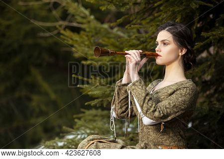 Portrait Of Calm Caucasian Female In Old Medieval Green Dress Playing The Flute Against Firtrees Out