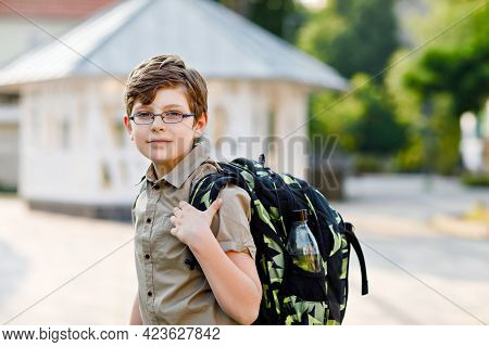 Happy Kid Boy With Glasses And Backpack Or Satchel. Schoolkid In On The Way To Elementary Or Middle