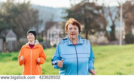 Portraits Of The Grandmother And Granddaughter Running Together. Mature And Young Women In Sports Cl