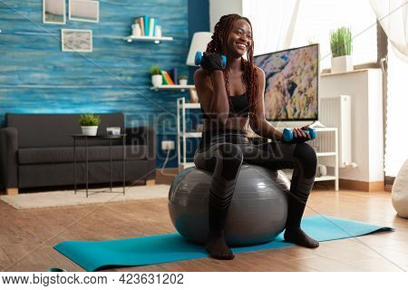 Smiling Cheerful African Woman Flexing Arm Working Out Biceps, Using Dumbbells Sitting On Stability