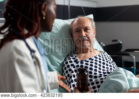 Close Up Of Sick Unwell Senior Man Patient Laying In Hospital Bed. Listening Doctor Specialist Discu
