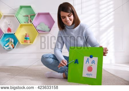 Happy Female English Teacher Giving Lesson Indoors. Early Childhood Education