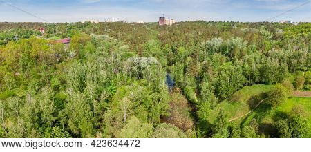Small Lake Overgrown With Reeds Among The Surrounding Forested Hills In Early Summer, Panoramic Aeri
