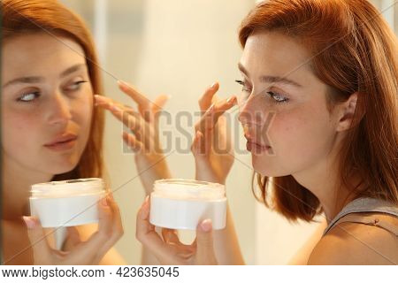 Woman Hydrating Face Skin In Front A Mirror Applying Moisturizer Cream On Cheek