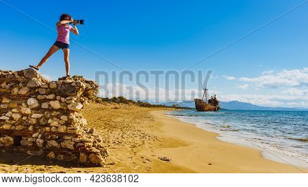 Tourism Vacation And Travel. Woman Tourist On Beach Taking Photo With Camera, Shipwreck In The Backg