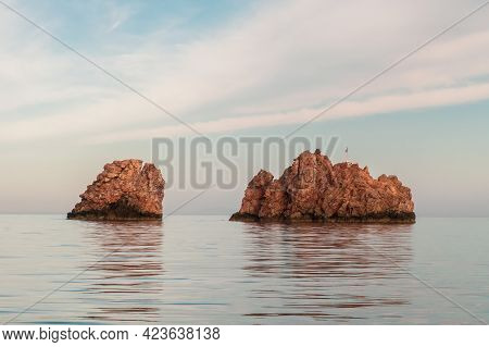 Nes Portes Rocks With A Cross On Top, North Of Paros Island Sticking Out From Perfectly Flat Mediter