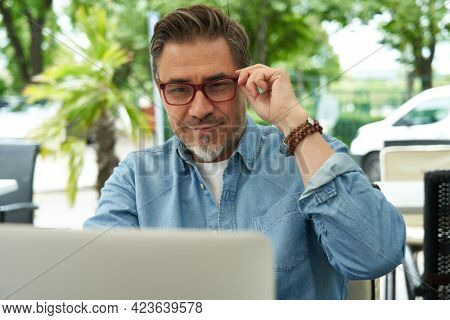 Outdoor portrait of mid adult man in 50s, happy confident smile. Working with laptop computer. Mature age, middle age, bearded, glasses.