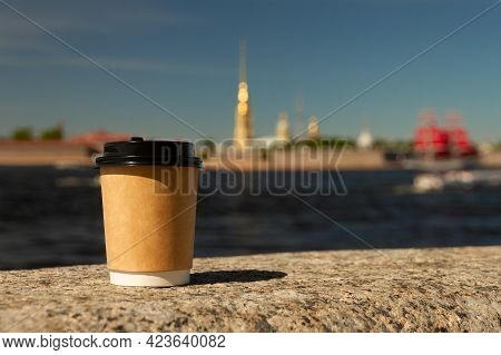 Brown Natural Paper Cup Of Ground Coffee On Granite Embankment Of Neva River Against Background Of P