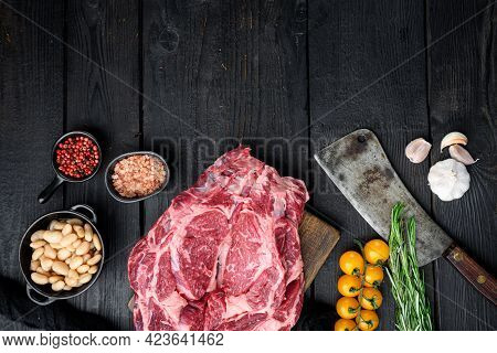 Raw Rib Eye Beef Marbled Meat  Steak With Pepper And Herbs Set, And Old Butcher Cleaver Knife, On Bl