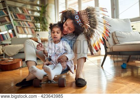 A young Mom with an indian headdress has wonderful time with her little daughter in a cheerful atmosphere at home. Family, together, love, playtime