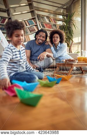 Young parents enjoying watching their little boy playing in a family atmosphere at home. Family, home, together, playtime