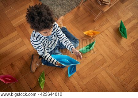 A little boy sitting on the floor and playing with paper boats in a playful atmosphere at home. Home, playtime
