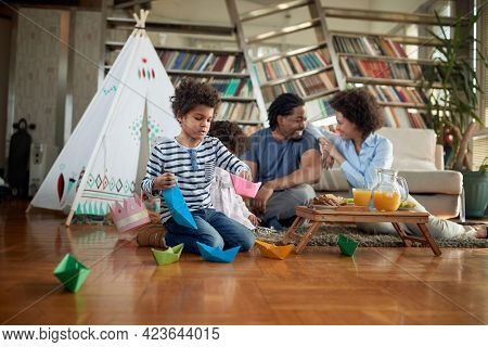 A young family spending a quality time in a cheerful atmosphere at home together. Family, home, together, playtime