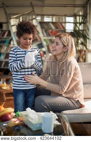Happy caucasian nanny babysitting afro american boy at home