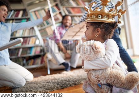 A little girl with teddy enjoys watching her family playing with swords  in a cheerful atmosphere at home. Family, together, love, playtime