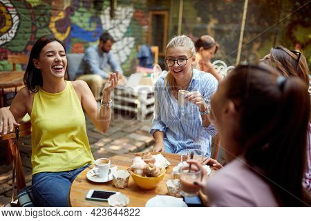 young adult caucasian woman telling funny story to her female friends, laughing
