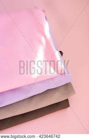 Colorful Cotton Folded Clothes Stack And The Rays Of The Sun. Stack Of Multicolored Clothes On Pink
