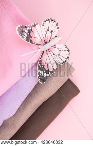 Colorful Cotton Folded Clothes Stack And Pink Butterfly. Stack Of Multicolored Clothes On Pink Backg