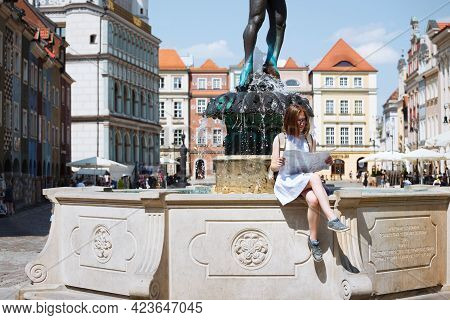 Girl Looking At The Map Sitting By The Fountain