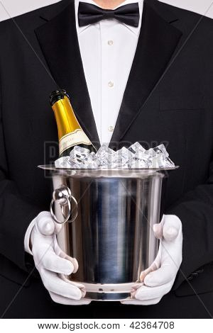 Waiter holding a wine cooler with a bottle of Champagne on ice