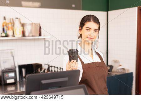 Beautiful Caucasian Barista Woman Show Takeaway Coffee Cup In One Hand At Coffee Bar