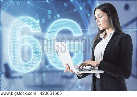 Attractive Businesswoman In Blurry Office Using Laptop With 6g Network Digital Hologram And Internet