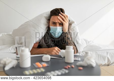 Shocked Sick Man In Medical Mask Looking At Table Full Of Medicine Pills, Lying In Bed Under Duvet