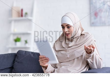 Discouraged Muslim Woman Gesturing While Using Digital Tablet On Sofa At Home