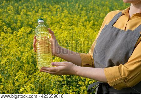 A Woman Stands In A Rape Field And Holds A Bottle Of Rapeseed Oil In His Hands. Concept Of Canola Oi