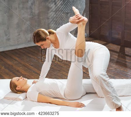 Professional Masseur Doing Thai Massage. Therapist Is Making Body Stretching Exercises To The Client