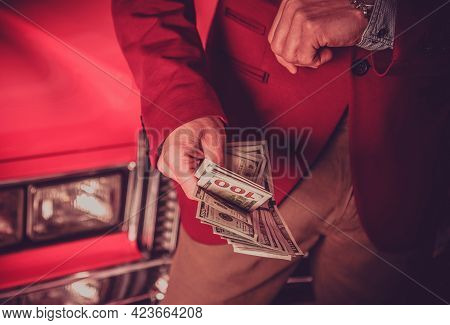 Caucasian Car Salesman With Cash Dollars In His Hands And Classic Red Car In A Background. Automotiv