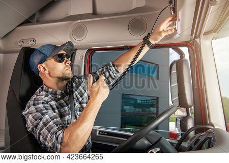 Caucasian Semi Truck Driver Talking By Cb Radio Inside His Truck Cabin. Transportation And Communica