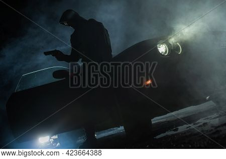 Caucasian Drug Dealer Wearing Hoodie With Firearm In His Hand Awaiting Someone Next To His Car. Nigh