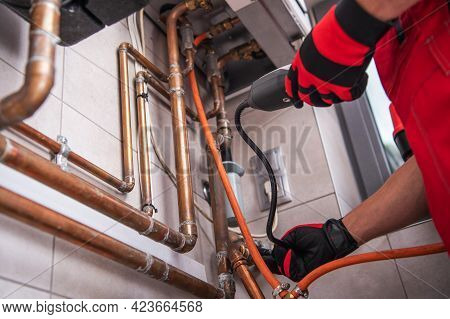 Hvac Worker With Natural Gas Detector Looking For A Leak. Residential Heating System Scheduled Maint