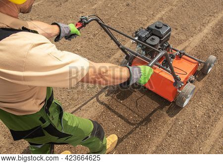 Preparing Soil For Grass Seeding By Aeration. Lawn Aerator Landscaping Job. Landscaping And Gardenin