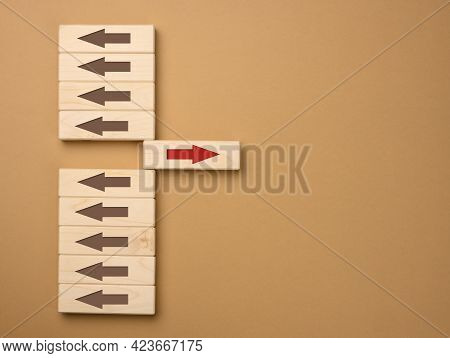 Wooden Blocks With Brown Arrows In One Direction And One Block With A Red Arrow In The Opposite Dire