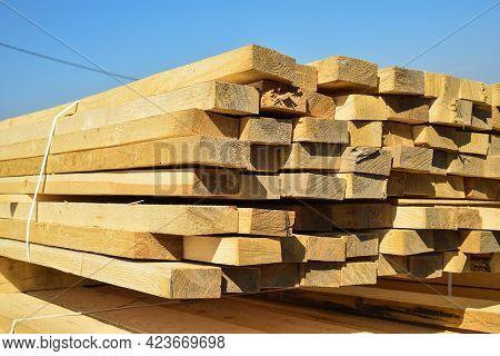 Stacked Lumber On Blue Sky.folded Wood.closeup Wooden Boards.the Surface Of The End Of The Board.lot