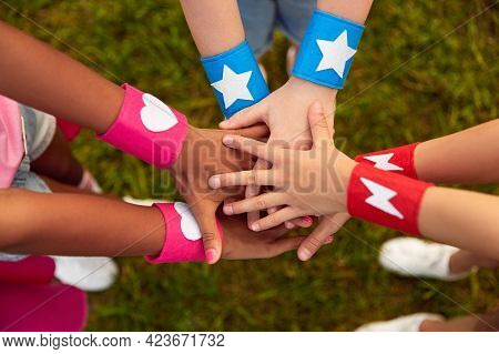 From Above Of Group Of Crop Anonymous Multiethnic Friends With Colorful Superhero Bracelets Stacking