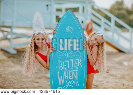 Two Young Pretty Blond Girls In Red Bikini Posing With Surfboards Against Blue Lifeguard Tower On Th