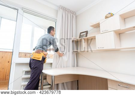 A Handyman Installing New Cornice For Curtains, Home Repair And Renovation Works
