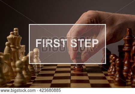 First Step Forward In Business Concept. Inscription On Image With Hand Moving Pawn On Chessboard, St