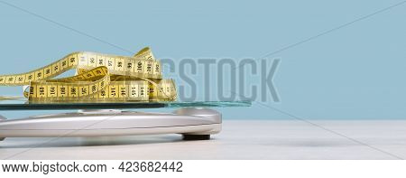 Yellow Tape Measure On Glass Bathroom Scale